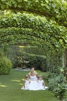 Two young girls and mid adult bride squatting under ivy arches portrait