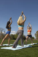 Two young women exercising with instructor in park