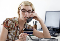 Woman holding a credit card while talking on the phone
