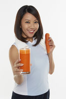 Popular : Woman holding a glass of carrot juice
