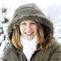 Woman in hooded jacket smiling at the camera