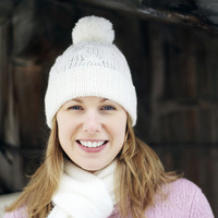 Woman in knitted hat and scarf smiling at the camera