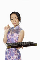 Woman in traditional clothing holding up an abacus