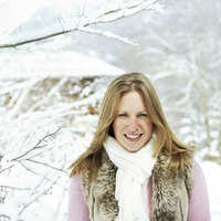 Woman in warm clothing smiling at the camera