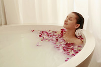 Popular : Woman relaxing in bathtub with flower petals