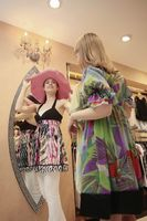 Woman trying on a hat while her friend is holding up a blouse