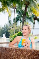 Woman with a glass of orange juice at the edge of pool