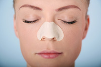 Woman with cleansing strip on her nose closing her eyes