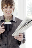 Woman with glasses holding cup and newspaper