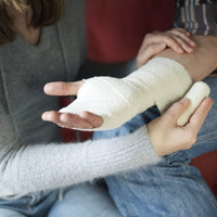 Woman wrapping man s injured hand