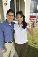Young couple holding keys outside new home portrait