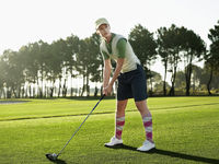 Popular : Young female golfer teeing off