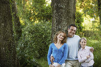 Popular : Young girl with parents leaning on tree in park portrait