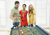 Young man with friends celebrating gambling win at roulette table