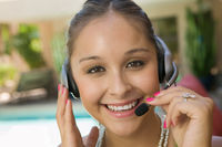 Young woman by swimming pool with headset close up portrait