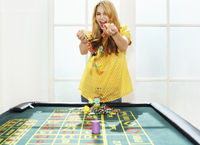 Young woman celebrating with chips on roulette table