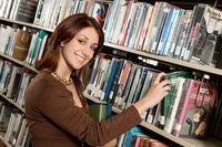 Young woman in library selecting book from shelf
