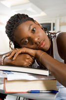 Young woman resting on stacked books  close-up   portrait