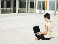 Young woman sitting in plaza courtyard  using laptop