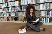 Young woman sitting on library floor reading