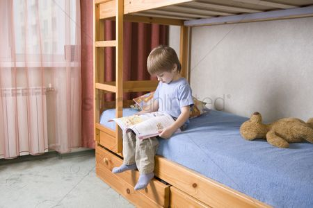 Toy : 5 year old boy sits on bunk  bed reading a book