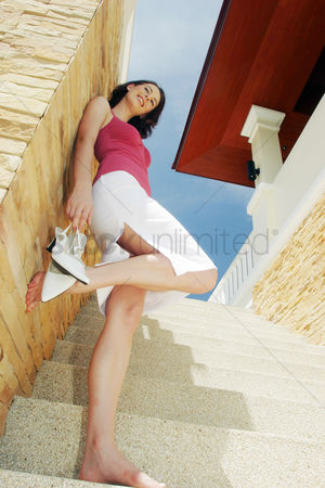 Stairs : A barefooted woman standing on the stairs holding her high heels