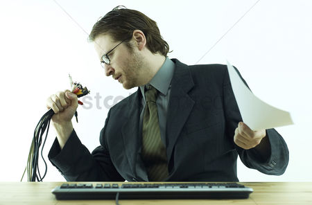 Bespectacled : A bespectacled guy in business suit looking at the bundle of computer plugs