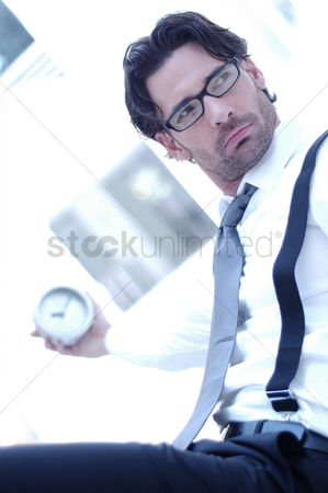 Bespectacled : A bespectacled man holding a clock