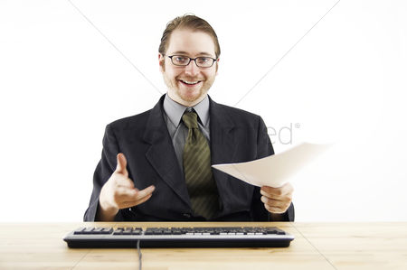 Determined : A bespectacled man in business suit looking happy sitting at his desk in the office