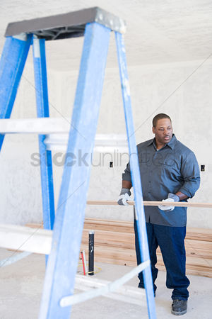 Interior : A builder holding a plank of wood