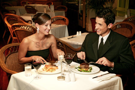 Girlfriend : A couple in dinners wear celebrating their anniversary by eating in the restaurant