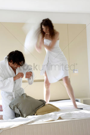 Fight : A couple pillow fighting on the bed