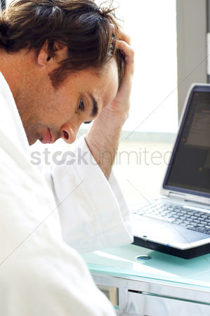 Pressure : A depressed looking man sitting in front of his laptop