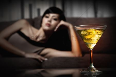 Fashion : A glass of martini  woman lying on the couch in the background
