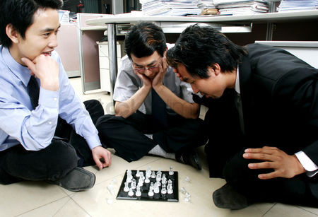 Having fun : A group of men playing chess in the office