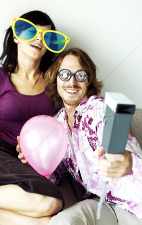Funny : A guy using instant camera to take the picture of him and his girlfriend in fun glasses