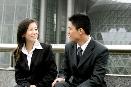 Sales person : A man and a woman in office attire talking