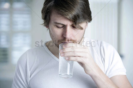 Medication : A man drinking a glass of effervescence