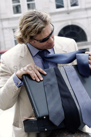 Choosing : A man in business suit and sunglasses choosing a suitable tie