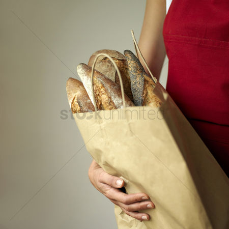 Adulthood : A woman holding a bag of breads