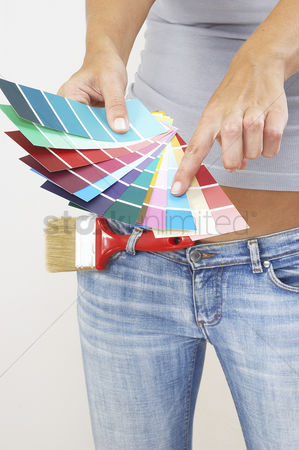 Paint brush : A woman in jeans pointing at the selected colour from the colour cards