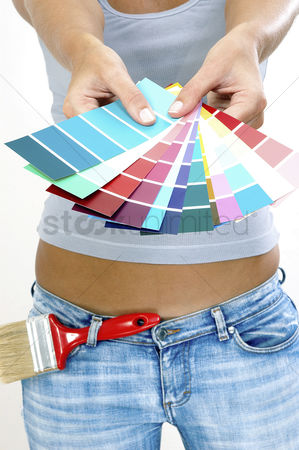 Paint brush : A woman in jeans showing colour cards