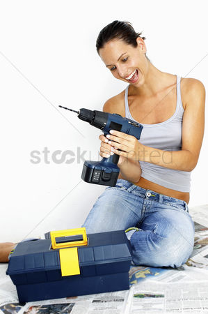 Excited : A woman in jeans sitting on the floor playing with a driller