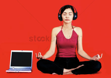 Notebook : A woman meditating with a headphone covering her ears and a laptop by her side