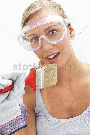Goggle : A woman with goggles and glove holding a brush