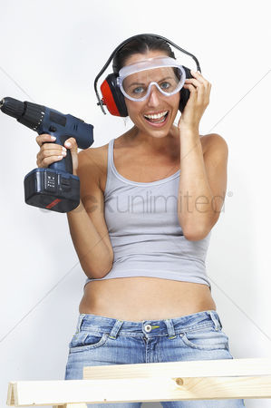 Goggle : A woman with goggles and headphone laughing while holding a driller