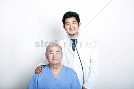 Examination : A young asian doctor with his hand on the shoulder of a senior adult patient