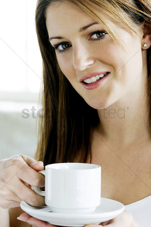 Adulthood : A young lady looking at camera while holding a cup of coffee