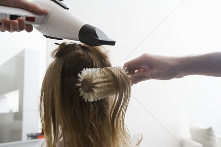 Profession : A young woman having her hair dried in the hairdressers