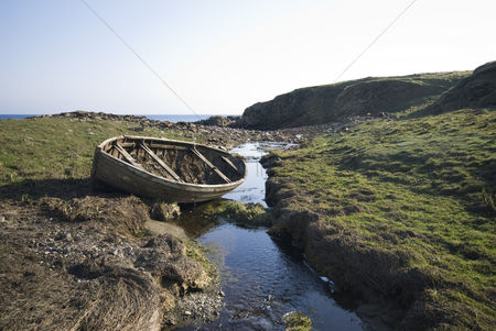 Grass : Abandoned boat by stream in peat